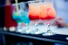 Bartender preparing a cocktail with blue and red syrup