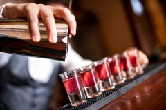 close-up of barman hand pouring alcohol into shot glasses in a n